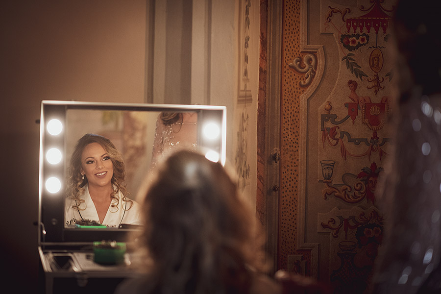 Wedding photographer in Chianti. Meleto Castle. Bride reflects in the mirror. Andrea Corsi wedding photographer in Tuscany