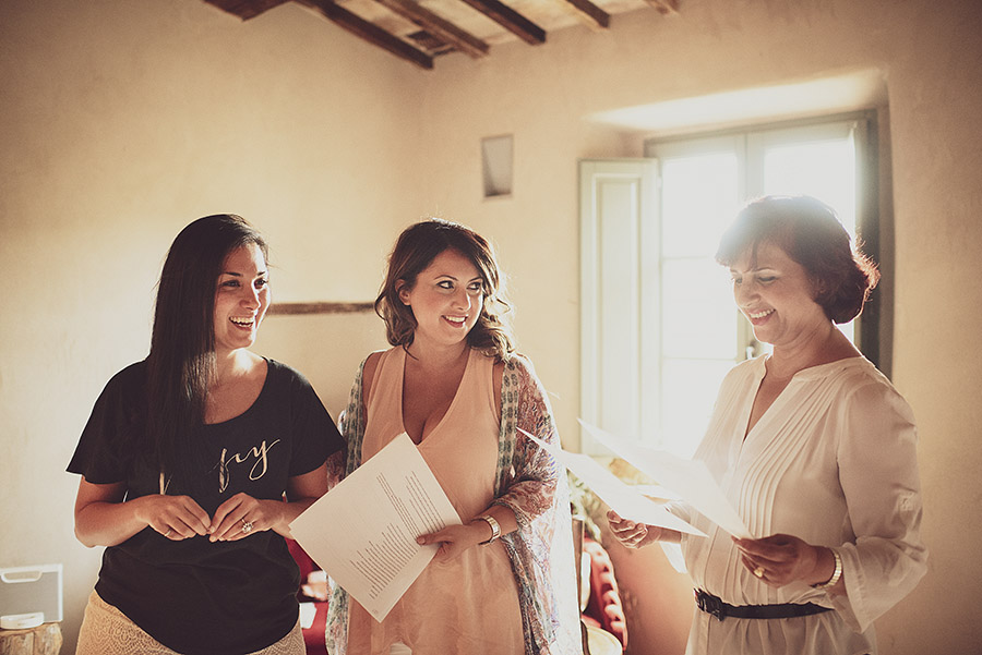 Three women reading. Wedding in Monte Follonico, Siena (Italy) countryside. Andrea Corsi wedding photographer, Tuscany.