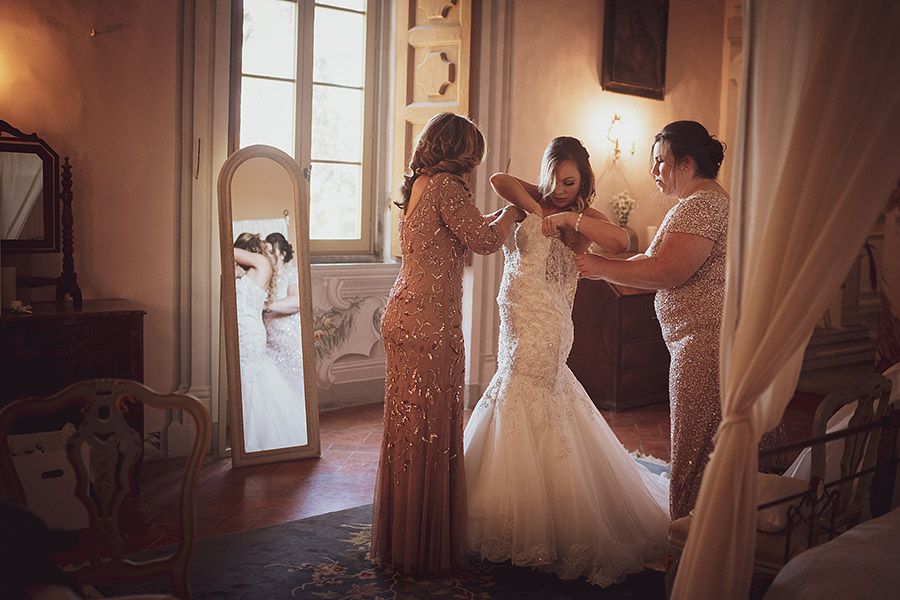 Two women helps brite wear the dress, Meleto Castle wedding. Andrea Corsi photographer