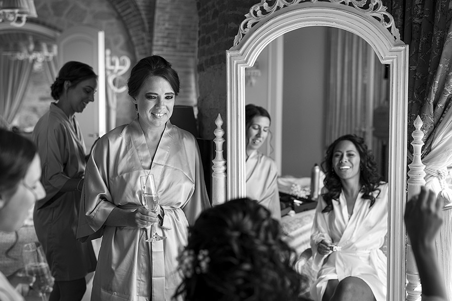 Woman in dressing gown and bride reflected in the mirror. Villa le Fontanelle wedding. Andrea Corsi photographer