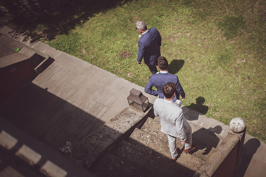 Three men go down the stairs. Villa le Fontanelle wedding. Andrea Corsi photographer